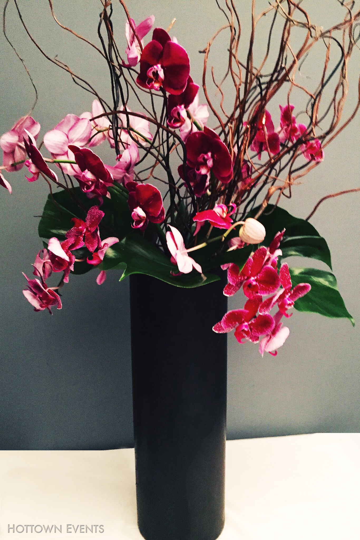 <h5>Red Orchids in large vase table top arrangement</h5>